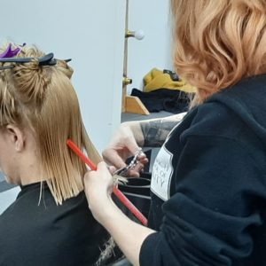 woman having a one length hair cut hairdressing course