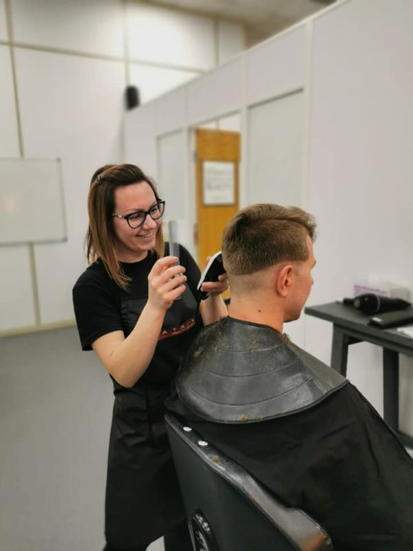 smiling barber cutting hair with clippers