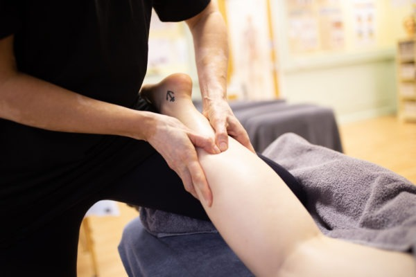 hands massaging back of leg