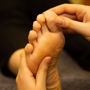 hand holding foot reflexology